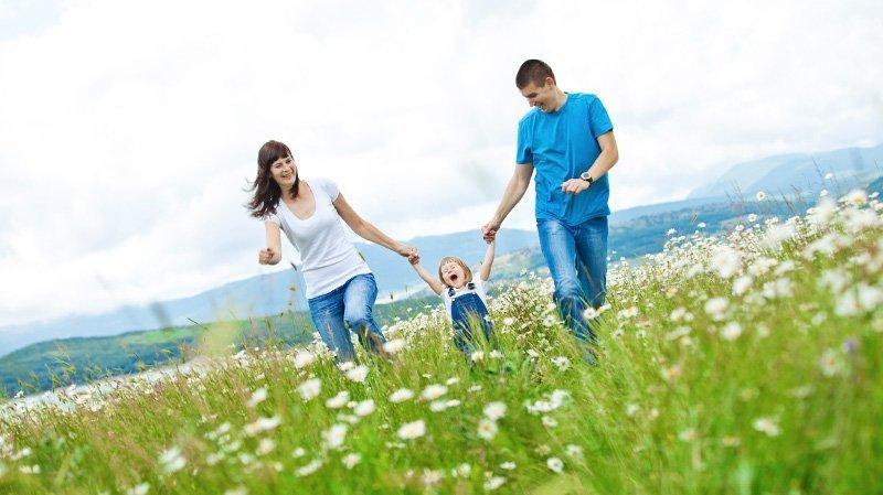 Una famiglia felice corre su un prato